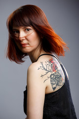 Image of woman with tattoo on back on empty gray background