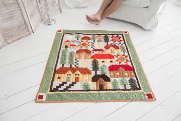 handmade, comfort, interior design concept. on the white wooden floor there is lovely and cosy blanket, it has adorable applique of different houses and trees