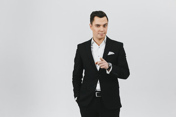 Stylish trendy young brunette man a in white shirt and black suit on white background