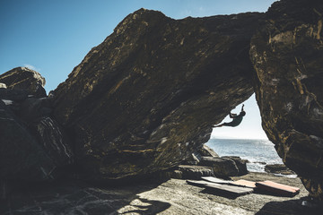 Silhouette of a climber climbing in a overhanging boulder problem close to the sea