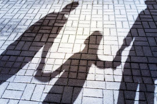 Schatten einer Familie,Kind schaut zu einem Elternteil