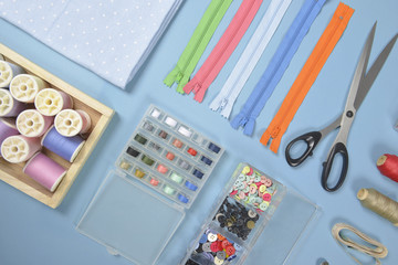 Flat lay of sewing material contains the fabrics, scissors, shirt buttons, zipper, pin and colorful thread rolls for sewing on two tone background, Sewing and needlework concept.