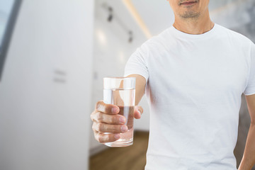 Man wearing white shirt holding glass of drinking water in a house, health care concept