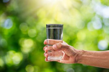 Hand holding drinking water in glass on blurred green bokeh background