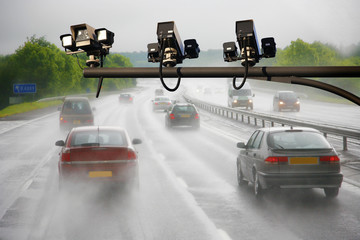 UK - Roads - heavy shower on a highway and road condition looks quite dangerous, speed camera present.