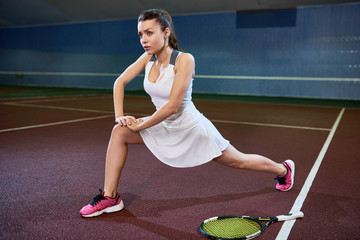 Full length portrait of female tennis player warming up and stretching before practice in indoor court, copy space
