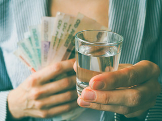 A glass of vodka and Russian rubles. The concept of alcoholism and a lot of money on alcohol.