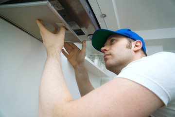 Handsome foreman fixing exhaust hood in the kitchen.