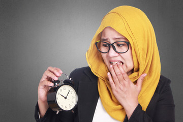 Muslim Businesswoman Late and Worried Looking at Clock