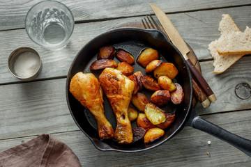 Fried chicken legs, fried potatoes in frying pan, top view