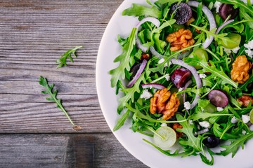 green salad bowl with arugula, walnuts, goat cheese, red onion and grapes
