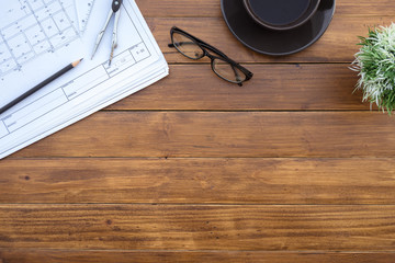 Flat lay of top view desk work table architect with drawing home plan building and stationary on antique brown wood table in home office includes copyspace for add text or graphic