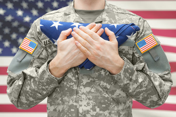 U.S. Army soldier holding folded USA flag before his chest