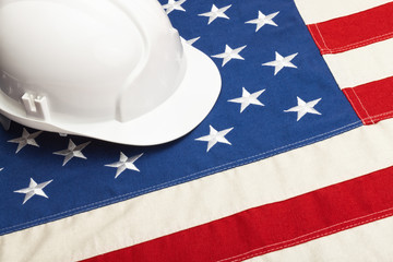 Close up studio shot of a white color construction helmet laying over USA flag