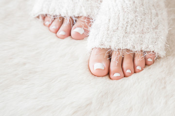Beautiful groomed woman's feet in the white socks warming on the fluffy mat in winter time.