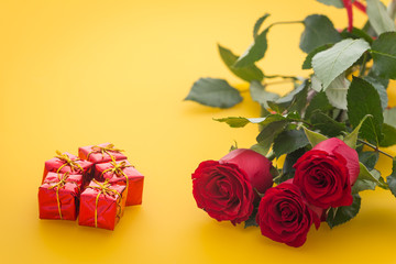 occasional beautiful red roses with boxes of gifts on the yellow background with place for dedications or wishes
