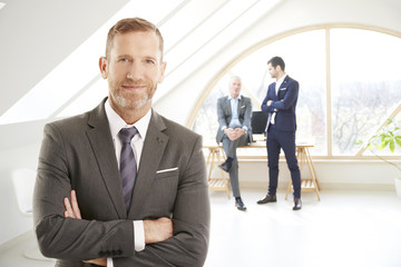 Successful businessman portrait. Senior investment advisor businessman wearing suit while standing at the office and looking at camera. Uncrecognizable business people standing at the background.