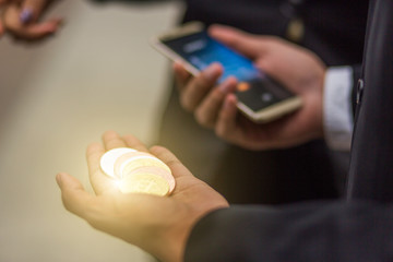hand with crypto currency and other hand try to exchange by smart phone