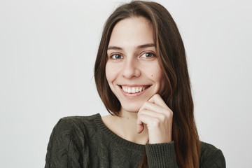 Cheerful good-looking young woman in green sweater with dark hair smiling happily, receiving positive news. Attractive beautiful girl with looking at camera with joyful smile