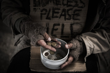 Homeless hands hold the bowl and count money inside