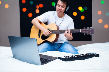 asian male musician composing a song with laptop computer & midi keyboard, practicing guitar with online music lesson on white bed at night. song writing, music education & bedroom studio concept