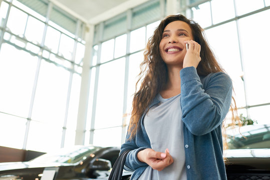 Low angle view of attractive mixed race woman looking away with charming smile and talking to her friend on smartphone while choosing new car in showroom, portrait shot