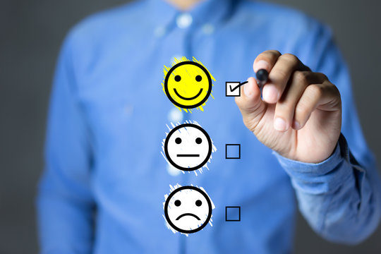 Businessman hand putting check mark a checkbox on excellent smiley face rating for a satisfaction survey, Customer experience concept.