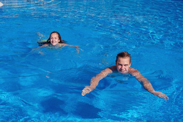 boy and girl having fun in swimming pool