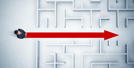 Business man looking at maze with red arrow