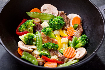 stir fried vegetables with meat in a wok