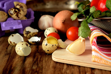 Ingredients for cooking fried eggs with vegetables on wooden background
