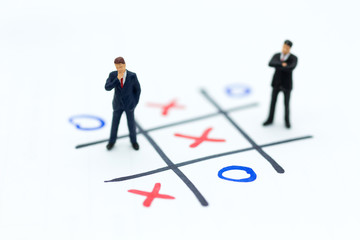 Miniature people: Businessmen stand on XO game board. Image use for business competition concept.