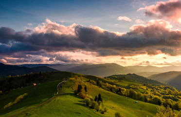 glorious cloudy sunset over rural area. beautiful springtime landscape with mountain ridge in the distance. country road winds through grassy slopes on rolling hill