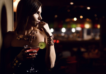 Beautiful sexy fashion brunette woman in expensive interior restaurant drink martini cosmopolitan cocktail
