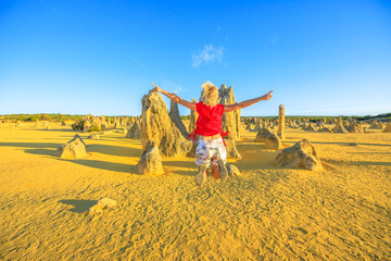West Australia travel freedom concept. Happy caucasian woman jumping at Pinnacles Desert in Nambung National Park, Cervantes. Aerial view of female jumper over limestone formations in WA, Australia.