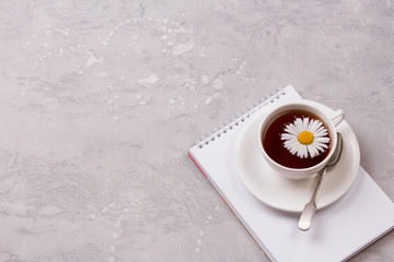 cup of tea with chamomile flowers on grey stone background