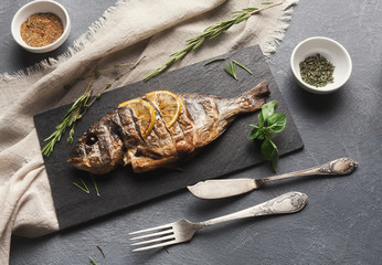 Whole grilled dorado with lemon slices on table