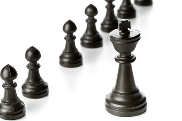 King chess figure in front of row of pawn chess figures