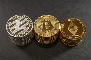 Three stack of cryptocurrency coins. Bitcoin, litecoin and ethereum