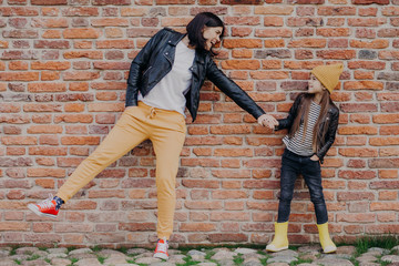 Small fashionable girl and her mother have fun together, keep hands together, pose against brick wall. Stylish young mum and daughter play outdoor. Relationships, good mood and fashion concept Wall mural