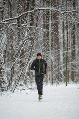 Picture of man in sportswear, black hat jogging in winter
