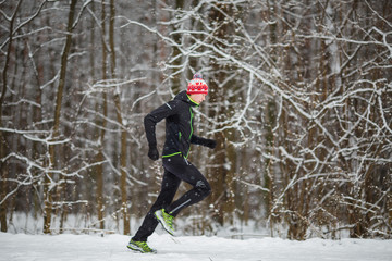 Image from side of man in sportswear, red cap on run in winter