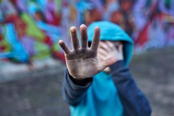 dramatic portrait of a little homeless boy, dirty hand