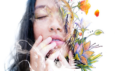 Paintography. Double exposure close-up of a sensual peaceful asian model gently touching her face combined with hand drawn ink and watercolour paintings with floral motifs