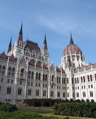 the historic hungarian Parliament building in Budapest with domes spires and blue sky