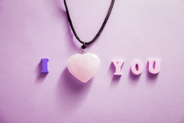 I love you lettering with a heart necklace on purple background. Valentine's day concept.