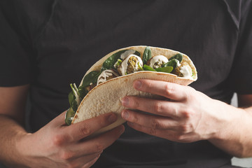 Vegan falafel with vegetables and tahini dressing in tortilla in the hands of a man. Vegan healthy food, Arabic food.