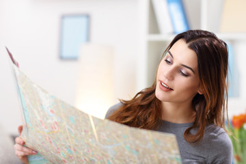 Happy woman with map at home planning holidays
