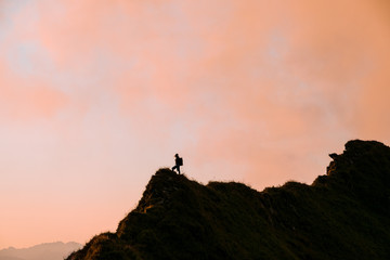 Sunset in the Algau region of Germany- mountain ridge with female hiker during golden hour with dramatic orange clouds