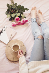 Young Caucasian woman in bed early in the morning, wearing distressed jeans and a white sweater and holds a cup of coffee. Roses and notebooks around. Cozy blogger mornings